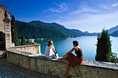 Two people enjoying view from church Santa Maria del Sasso, Morcote, Lago di Lugano, Ticino, Switzerland