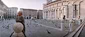 Man and pigeons on square in Lucca, Tuscany, Italy