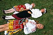 Young women in traditional costumes sunbathing on meadow, traditional celebration, Tallinn, Estonia