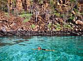 Woman Swimming in natural pool, Galapagos Islands, Ecuador