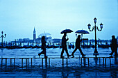People are walking in the rain over the flooded Gorgio Maggiore in Venice, Italy