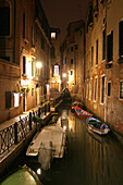 Beleuchteter Kanal mit Booten bei Nacht in Venedig, Italien