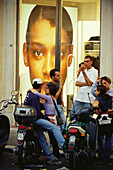 Young people with scooters in front of an advertisement, Rome, Italy, Europe