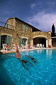 Woman jumping in a pool in front of a country house, Cote d´Azur, France, Europe