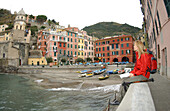 Eine Frau sitzt auf dem Hafenmauer, Entspannung nach einer Wanderung, Riomaggiore, Cinque Terre, Italy.