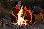 Two women sat around the campfire, Camping, Andalusia, Spain