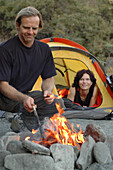 Couple camping, man cooking on a campfire, Camping, Andalusia, Spain