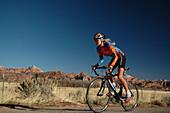 Woman riding a racing bike through Zion National Park, Zion National Park, Springdale, Utah, USA