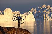 Female mountainbiker carrying her bike, admiring the views, Ilulissat, Greenland
