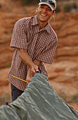 A man putting up a tent, Camping, Lake Powell, Arizona, USA