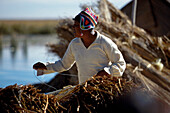 Indian building a boat, Puno, Lake Titicaca, Peru, South America, America