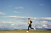A jogger running in a meadow, Stubaital Valley, Tyrol, Austria