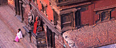 Woman sitting in front of a temple on a step, Durbar Square, Patan, Nepal, Asia