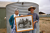 Descendants of Afghan cameleers, Marree, Australien, South Australia, Afghans with photo of camel in Marree. Marree was once where cattle was loaded onto the famous Ghan Train, Marree is at the junction of the Birdsville and Oodnadatta Track, Grandmother
