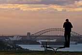 Photographing the Harbour Bridge, Australien, Sydney Harbour Bridge, Abendlicht, Tourist taking a photo of the Harbour Bridge and Opera House at sunset, from park bench
