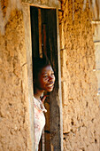 African Woman standing in door of a clay hut, Sansibar, Tansania, Africa