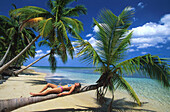 Woman lying on palm tree, sandy beach, Dominican Republic