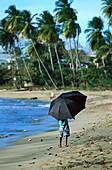 Junge mit Sonnenschirm am Strand, Tobago West Indies, Karibik