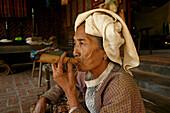 portrait of eldery woman smoking cheerot cigar, Myanmar