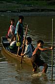 School children in boat, Dorfkinder, kommen mit dem Boot von der Schule