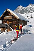 Menschen mit Schneeschuhen und Schlitten vor verschneiter Berghütte, Ramsau, Steiermark, Österreich, Europa