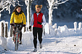 Frau auf einem Fahrrad neben Joggerin auf verschneiter Strasse, Ramsau, Steiermark, Österreich, Europa