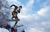 Man wearing traditional costume with wooden skis during a jump, Austria, Europe