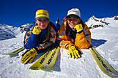 Teenager mit Ski, liegend im Schnee