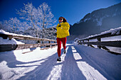 Woman jogging on snow covered track under blue sky