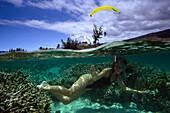 Paraglider and woman snorkeling, Ile de la Reunion, France, Europe