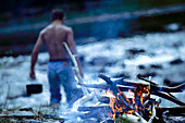 Campfire, topless man in background, riverside of Isar, Upper Bavaria, Germany