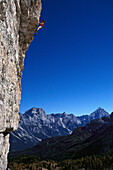 Man freeclimbing at rock face, Dolomites, Italy