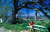Woman sit on a bench under oak, Agios Minas, South Cyprus Cyprus