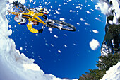Mountainbiker jumping through snow, Alps, Austria