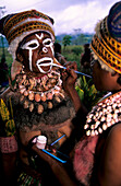 Woman painting the face of another woman in preparation for the Huli Sing Sing celebrations, Mt Hagen, Eastern Highlands, Papua New Guinea, Melanesia