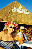 Couple having a cocktail drink at the Yacht Club, Bora Bora, Windward Islands, French Polynesia, South Pacific
