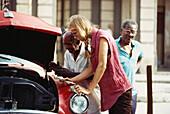 People repairing a vintage car, Havana, Cuba, Caribbean, America