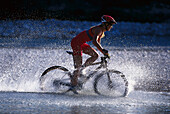 Female mountainbiker passing river, Bavaria, Germany
