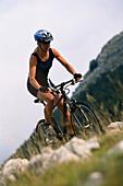 Female mountainbiker riding over Campo Imperatore, Abruzzo, Italy