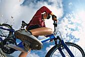 Female mountainbiker braking, smiling at camera, Abruzzo, Italy