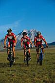 Three mountain bikers on an alpine meadow, Campo Imperatore, Abruzzi, Italy, Europe
