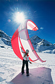 Young woman kiteboarding in snow, holding kite, Lermoos, Lechtaler Alpen, Tyrol, Austria