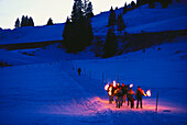 People walking with torches through snowcovered scenic, Arlberg, Vorarlberg, Austria