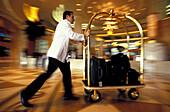Employee pushing luggage through hotel's entrance hall, Dubai, United Arab Emirates, Middle East, Asia