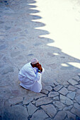 A man cowering in the shadow, Nizwa, Oman