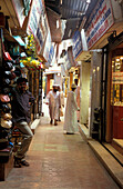 People going through narrow alley between shops, Souk, Muscat, Oman