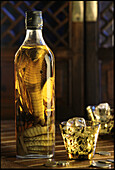 Bottle of spirits with pickled cobra and glass with ice cubes, Saigon, Vietnam, Asia