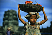 Girl carrying a basket of fruit on her head, Angkor Wat, Siem Raep, Cambodia, Asia