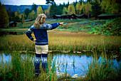 Norwegian woman standing in front of a pond, Maihaugen, Lillehammer, Norway, Scandinavia, Europe