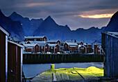 Rorbu Hütten in einem Fischerdorf unter Wolkenhimmel am Abend, Reine, Lofoten, Norwegen, Skandinavien, Europa